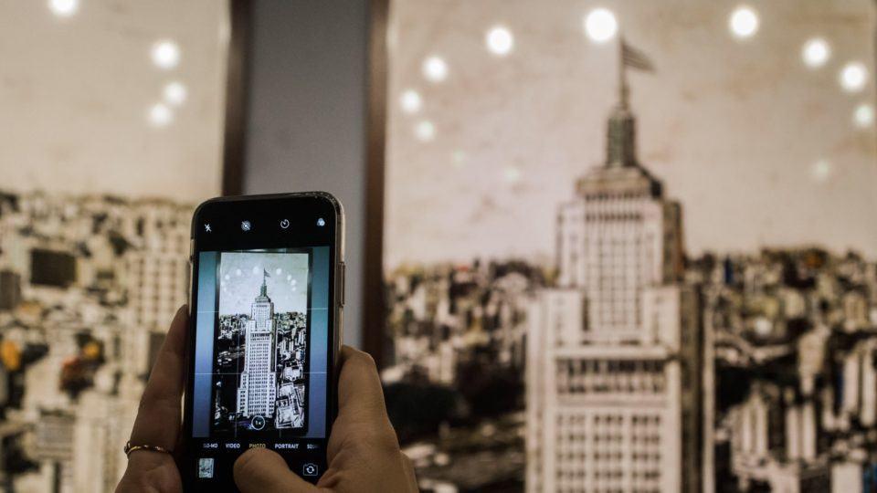 Celular tirando foto de uma foto antiga do Edifício Farol Santander.