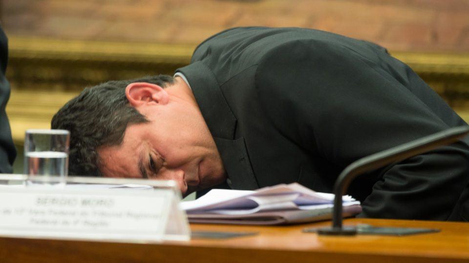 Sergio Moro deitado sobre uma mesa.
