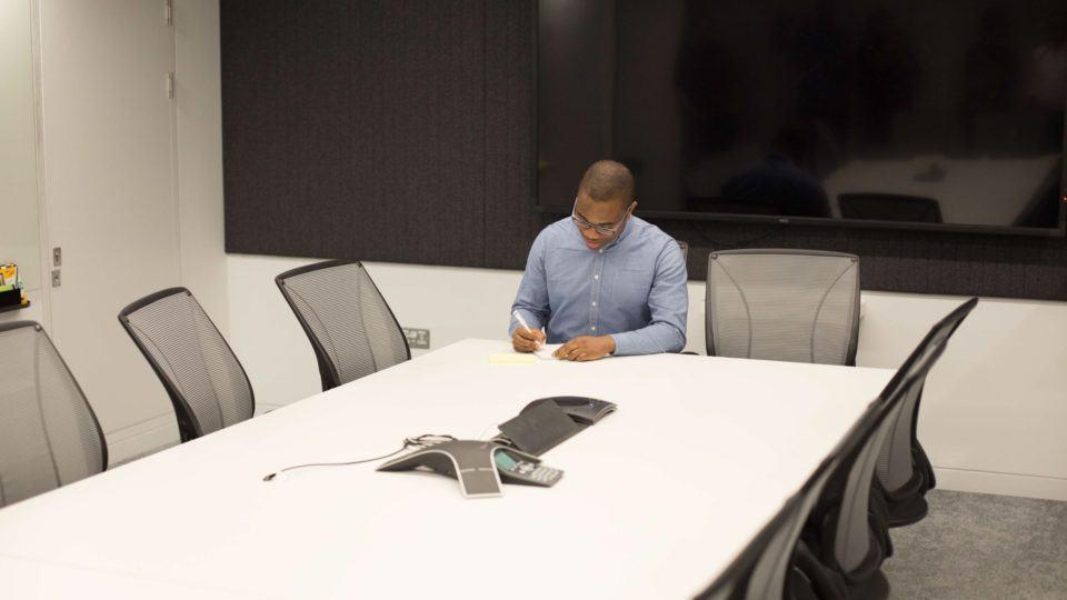 Homem negro sentado em uma sala de reuniões de empresa.