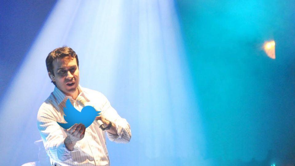 Montagem com o Pe. Fábio de Melo no palco segurando o pássaro (logo) do Twitter em uma das mãos.