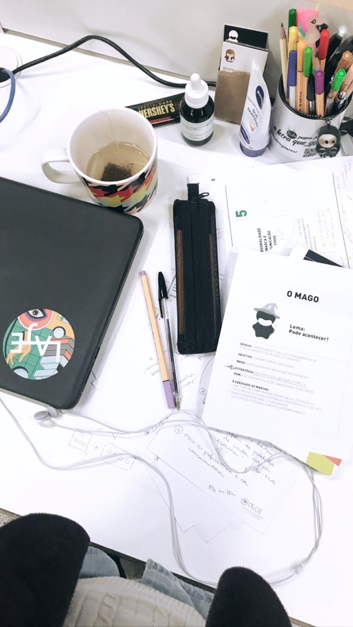 Mesa de trabalho da Beatriz cheia de canetas, papéis e com uma caneca de café.