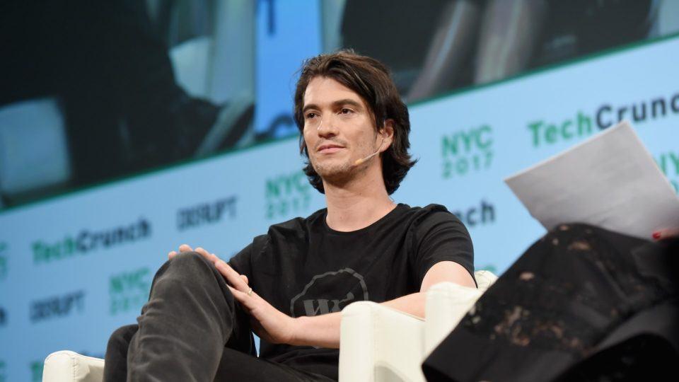 Adam Neumann sentado em um palco durante evento em Nova York.