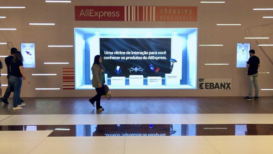 Telão da loja pop-up do AliExpress em destaque com mulher passando em frente.