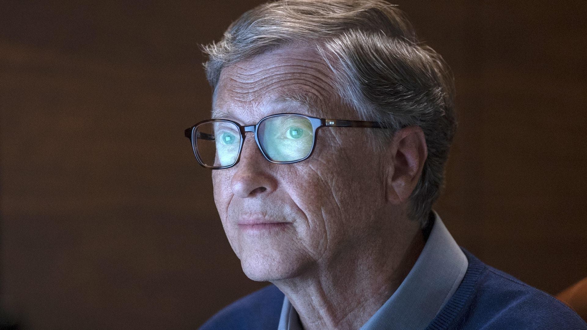 Close em Bill Gates de óculos com uma tela refletida nas lentes.