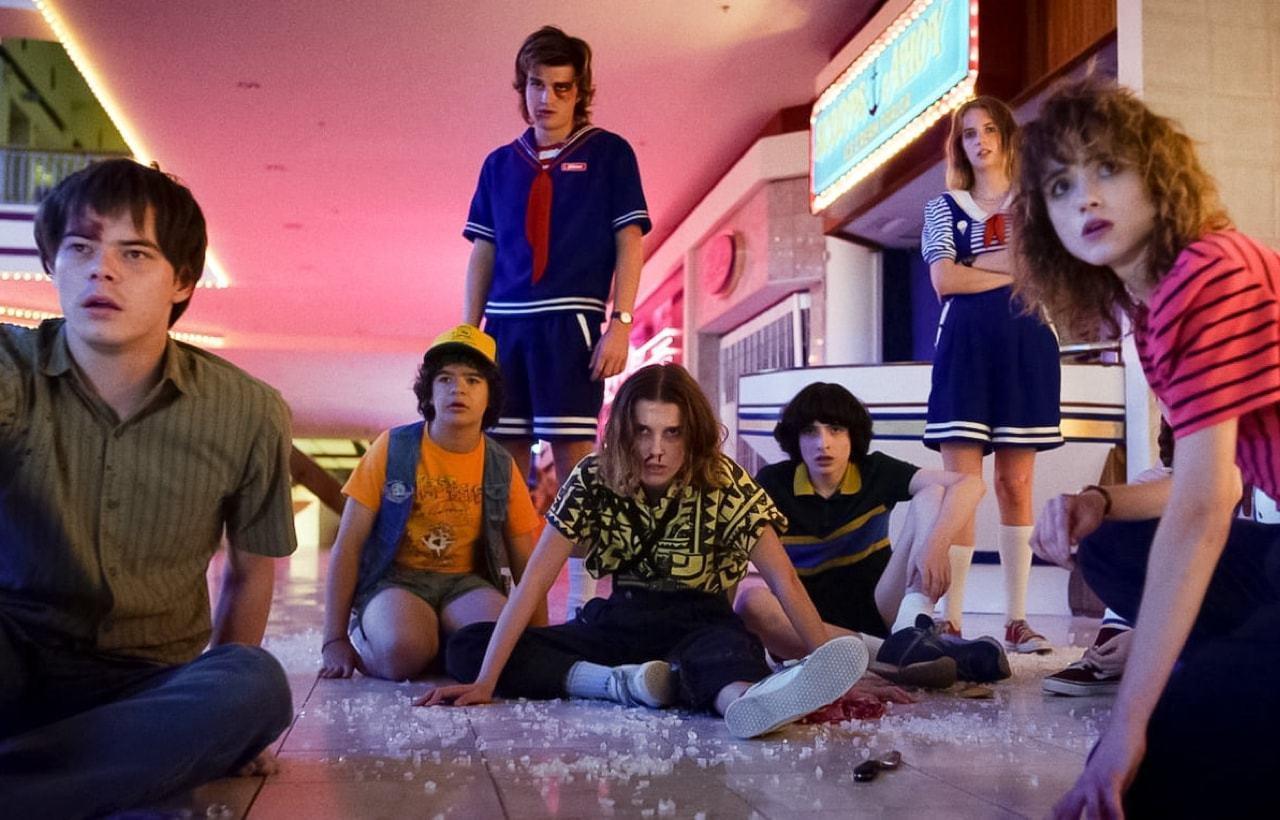 Cena de Stranger Things 3 em que os heróis da série estão abatidos no shopping olhando para uma nova ameaça.