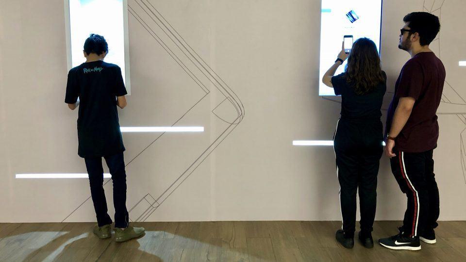 Pessoas interagindo com os telões e celulares expostos na loja pop-up do AliExpress.