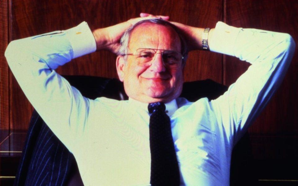 Lee Iacocca com os braços atrás da cabeça, como na capa da sua autobiografia.