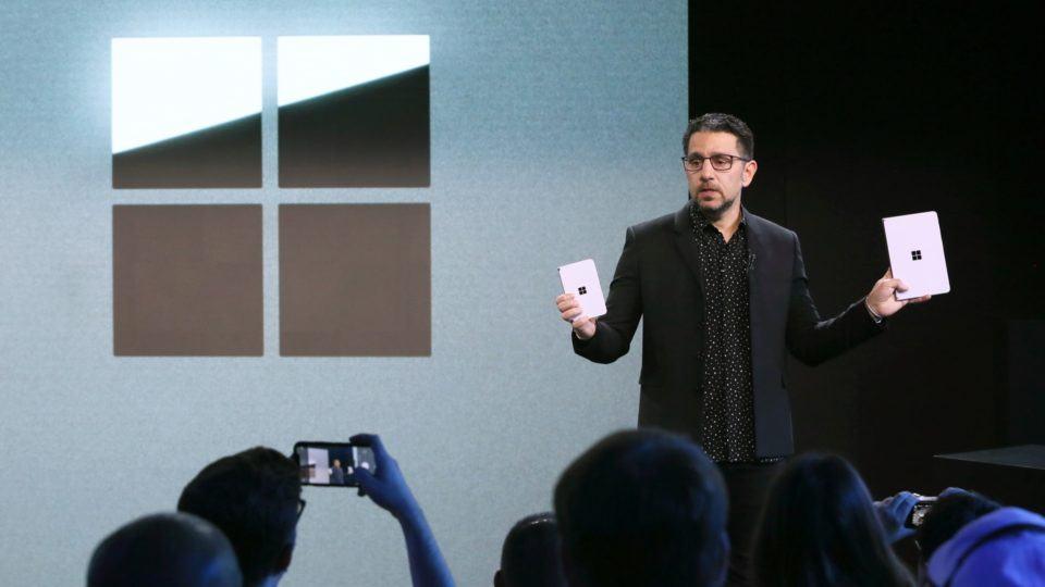 Panos Panay segura o Surface Duo e o Surface Neo no palco do evento da Microsoft, com o logo da empresa grande atrás.