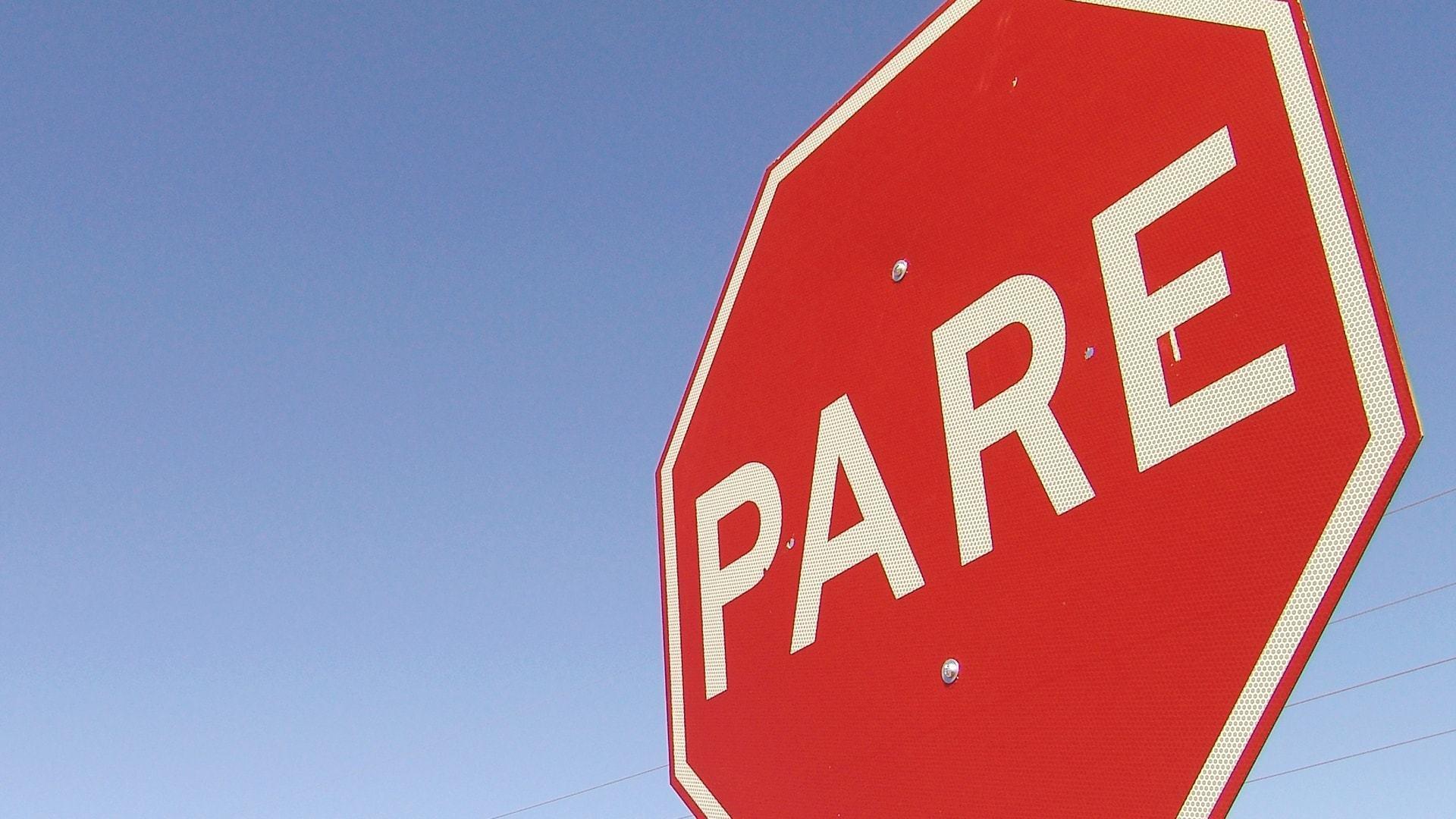"""Placa de trânsito vermelha com a inscrição """"Pare"""" contra um céu azul."""