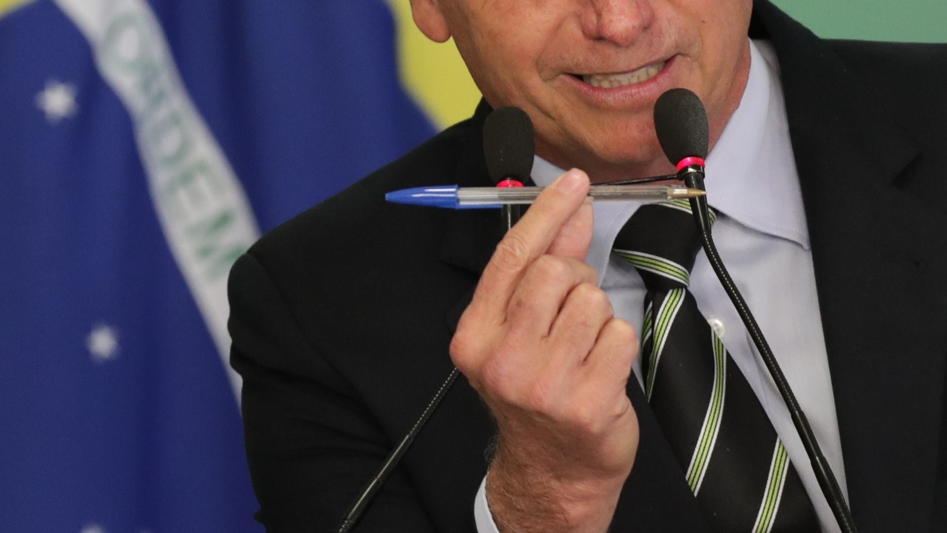 Presidente Jair Bolsonaro segura uma caneta BIC antes de assinar decreto de armas, em janeiro de 2019.