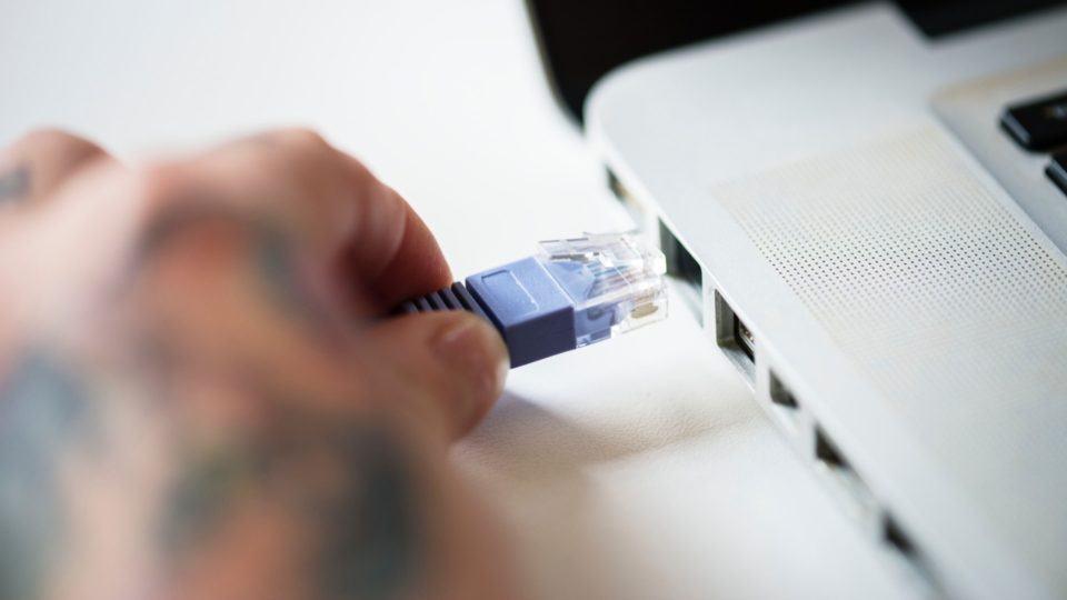 Pessoa conectando cabo da internet no notebook.