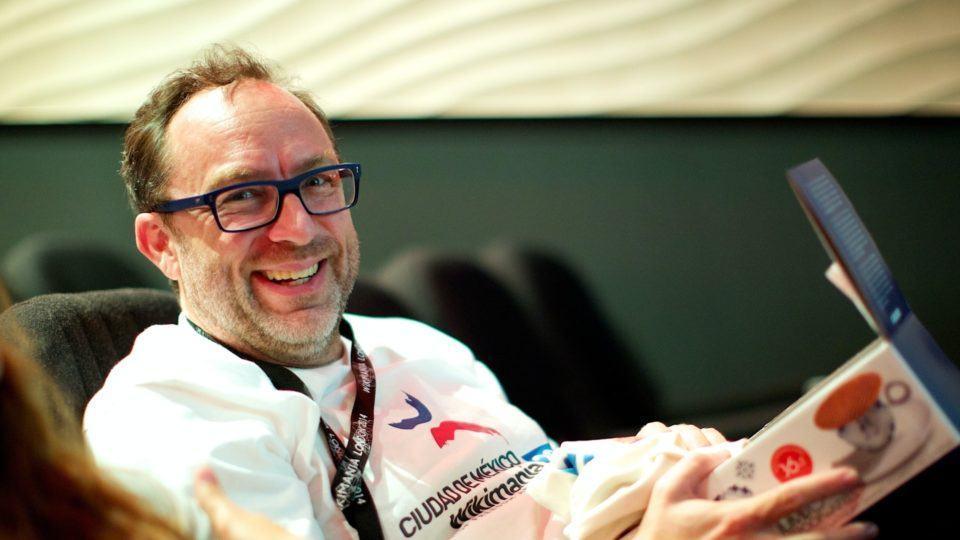 Jimmy Wales olha para a câmera e sorri enquanto segura um presente recebido na Wikimania 2014, em Londres.