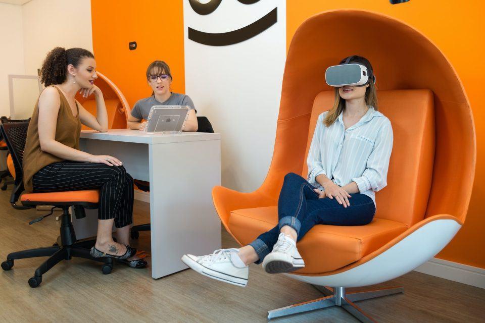 Três pessoas em uma sala da Beetools, decorada em tons laranja, uma delas sentada em uma poltrona grande usando um headset de realidade virtual.