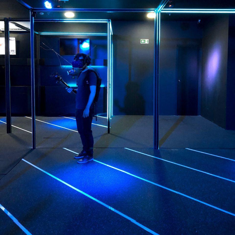 Homem com headset de realidade virtual andando em amplo espaço durante experiência Beleaf.