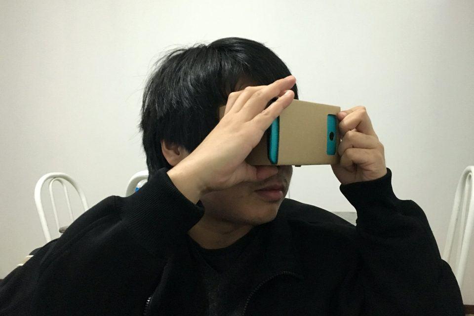 Close de um homem usando um headset de papelão (Google Cardboard) com um celular azul dentro.