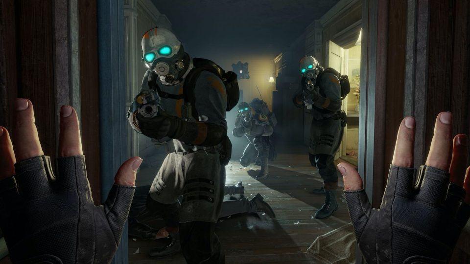 Tela do jogo Half-Life: Alyx mostrando as mãos da personagem principal (em primeira pessoa) encarando três inimigos portando armas.