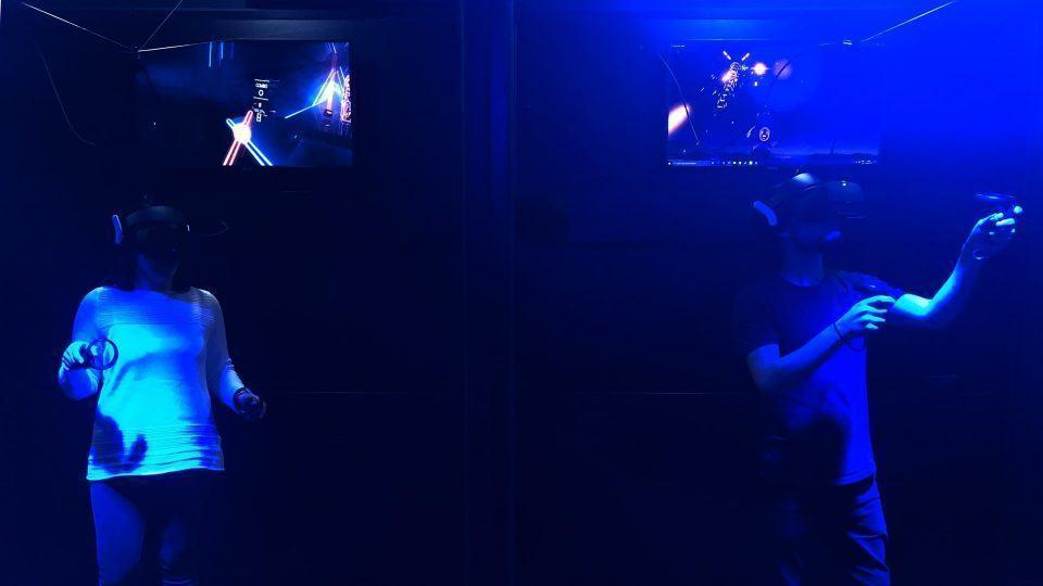 Duas pessoas usando headsets de realidade virtual em sala escura, com telas acima mostrando o que elas estão vendo.