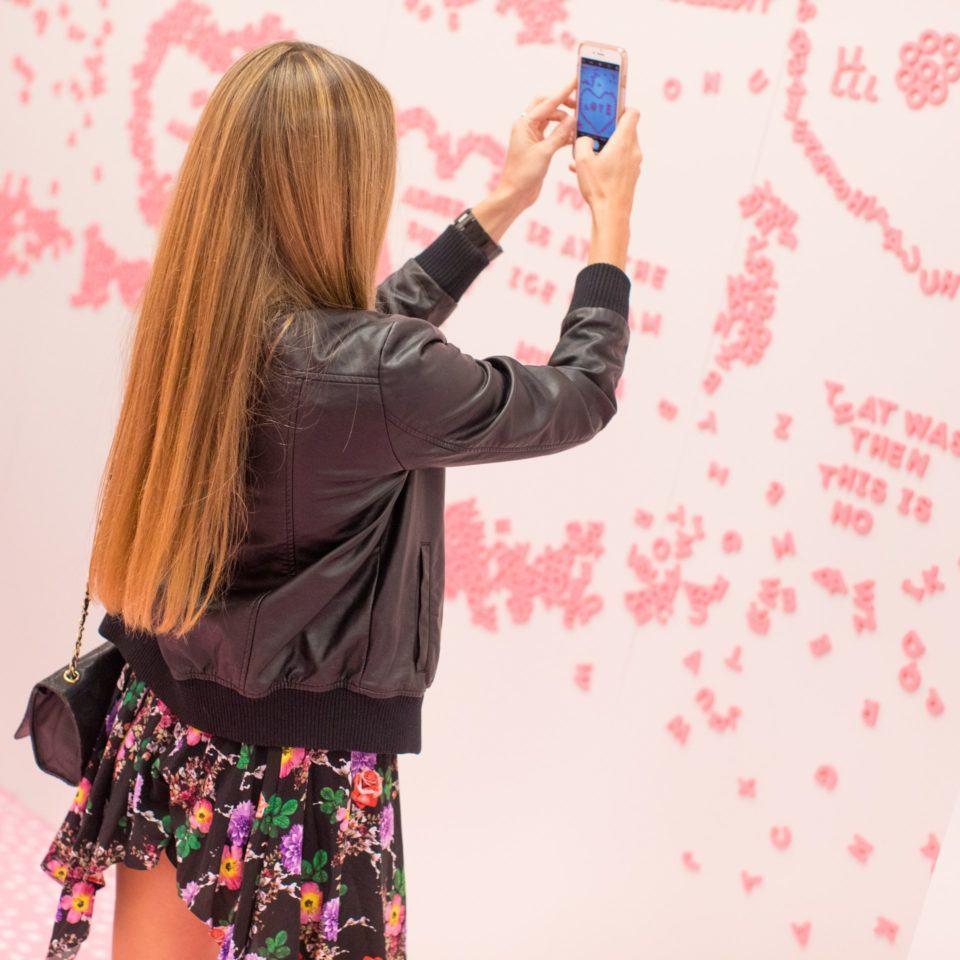 Mulher tirando foto de uma parede com letras que os visitantes usam para formar frases, no Museu do Sorvete.