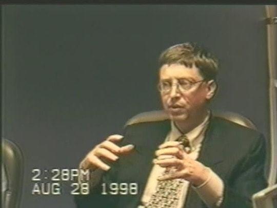 Bill Gates gesticulando; letreiro da câmera informando data e hora — 28 de agosto de 1998.