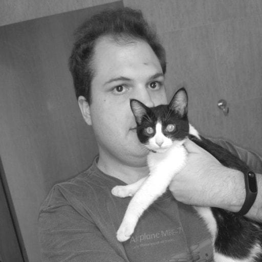 Caio Volpato segurando um gato malhado.