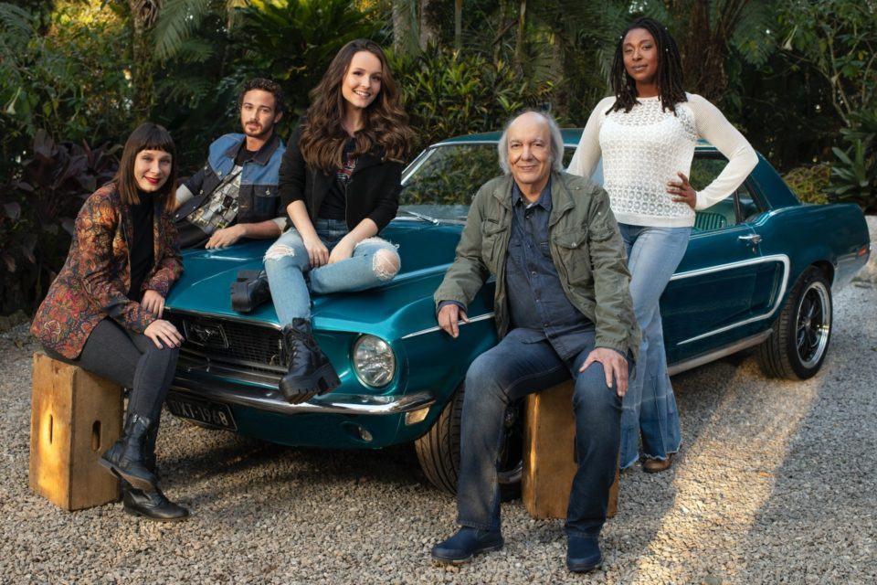 """Parte do elenco do filme """"Modo Avião"""" em torno do carro azul que Germano (Erasmo Carlos) conserta ao longo da história."""