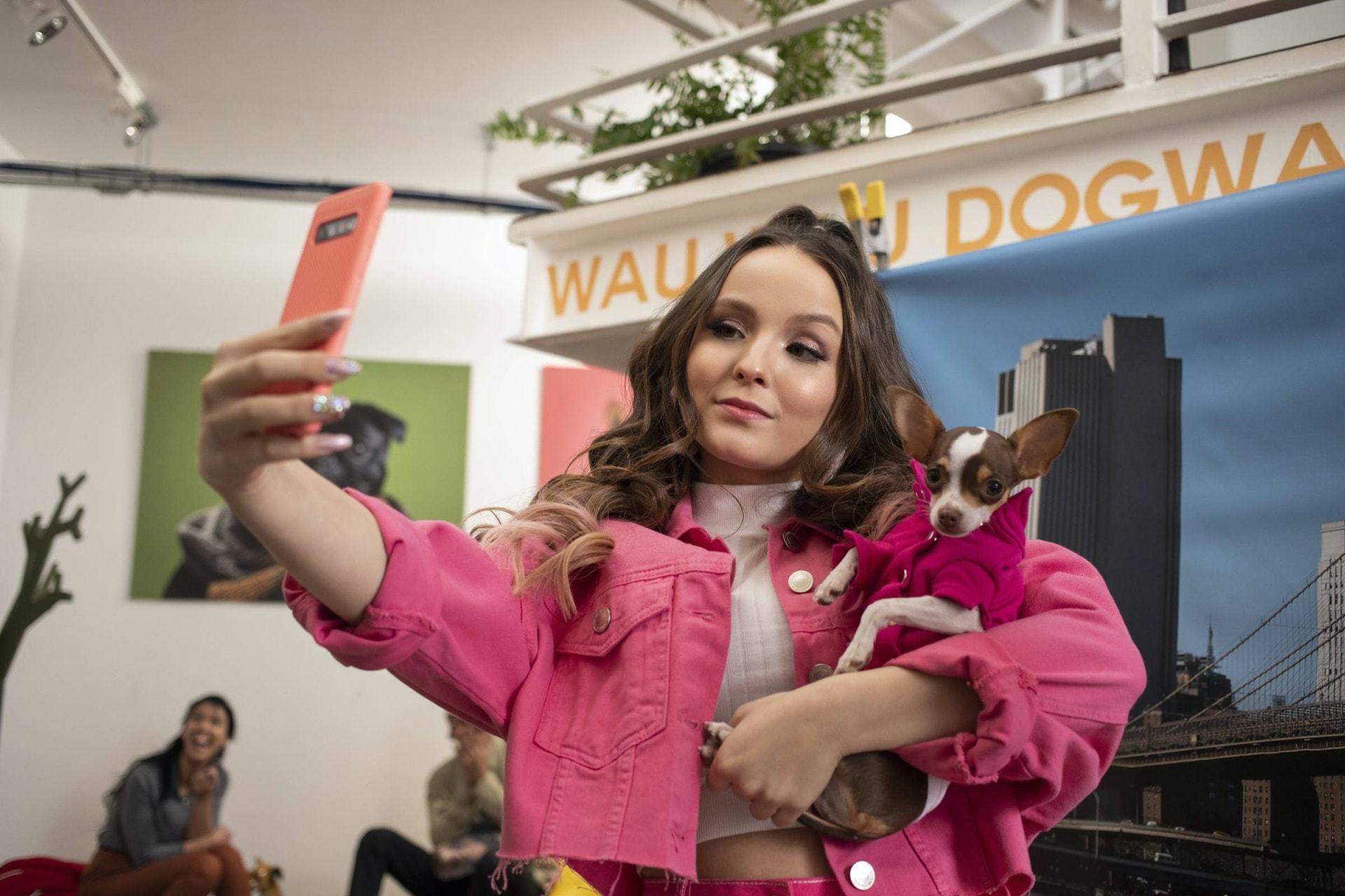 Larissa Manoela vestindo uma jaqueta rosa tira selfie com um cachorro no colo.
