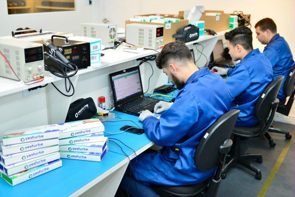 Três pessoas consertando celulares em uma bancada e, ao lado, pilha de caixas de celulares refabricados prontos.