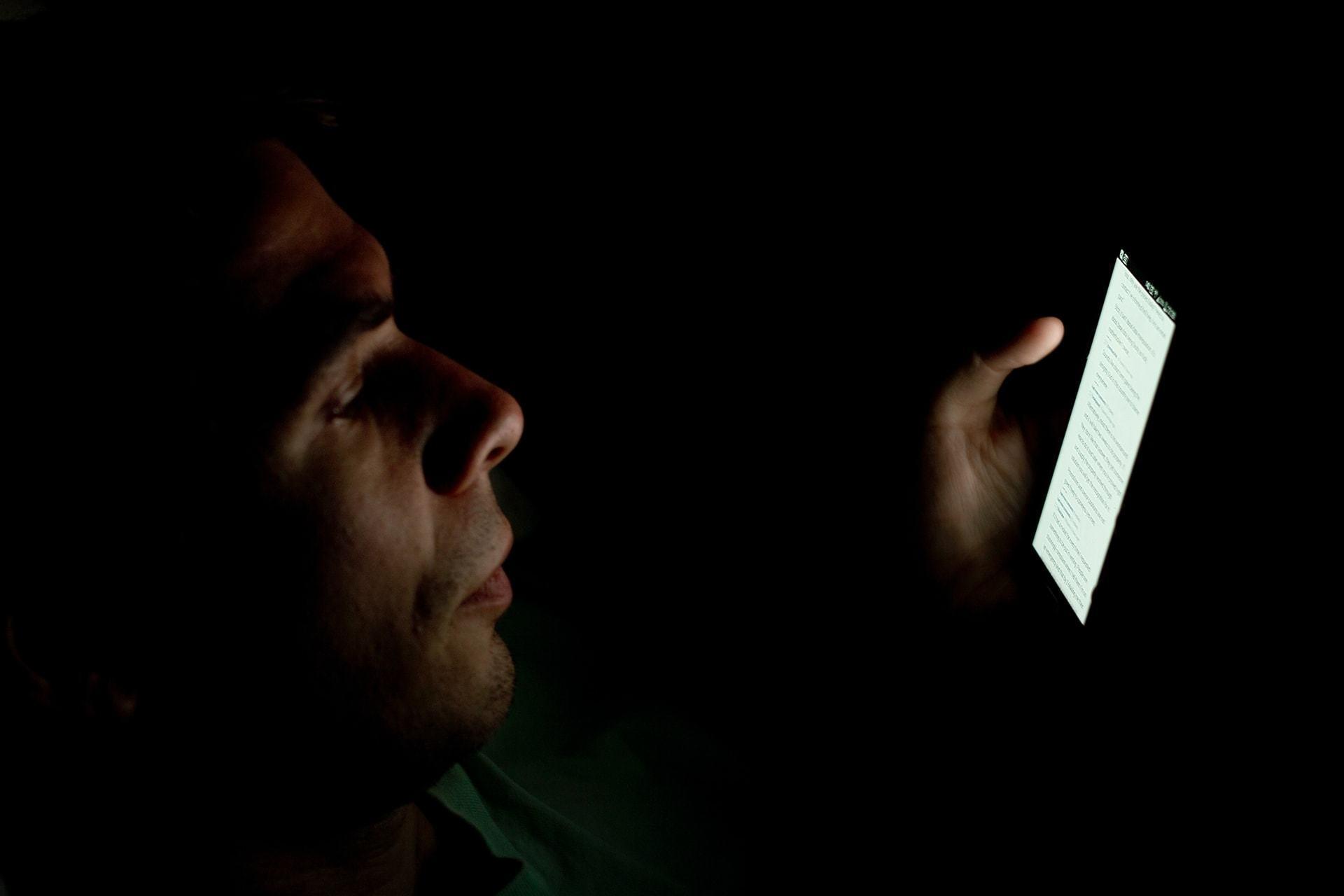 Homem com o rosto parcialmente iluminado mexendo no celular no escuro.