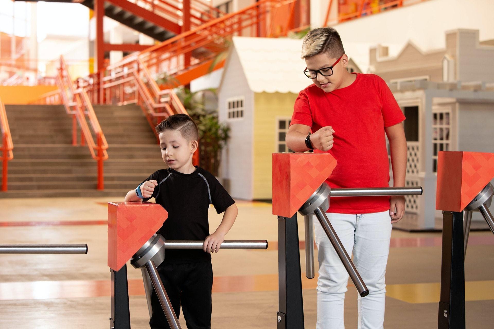 Duas crianças passando por catracas graças às suas pulseiras Schood.