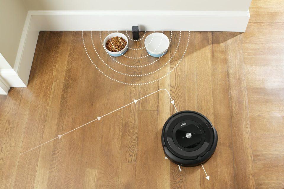"""Roomba no chão ignorando um canto da sala com comida de cachorro para demonstrar as """"paredes virtuais"""" do sistema."""
