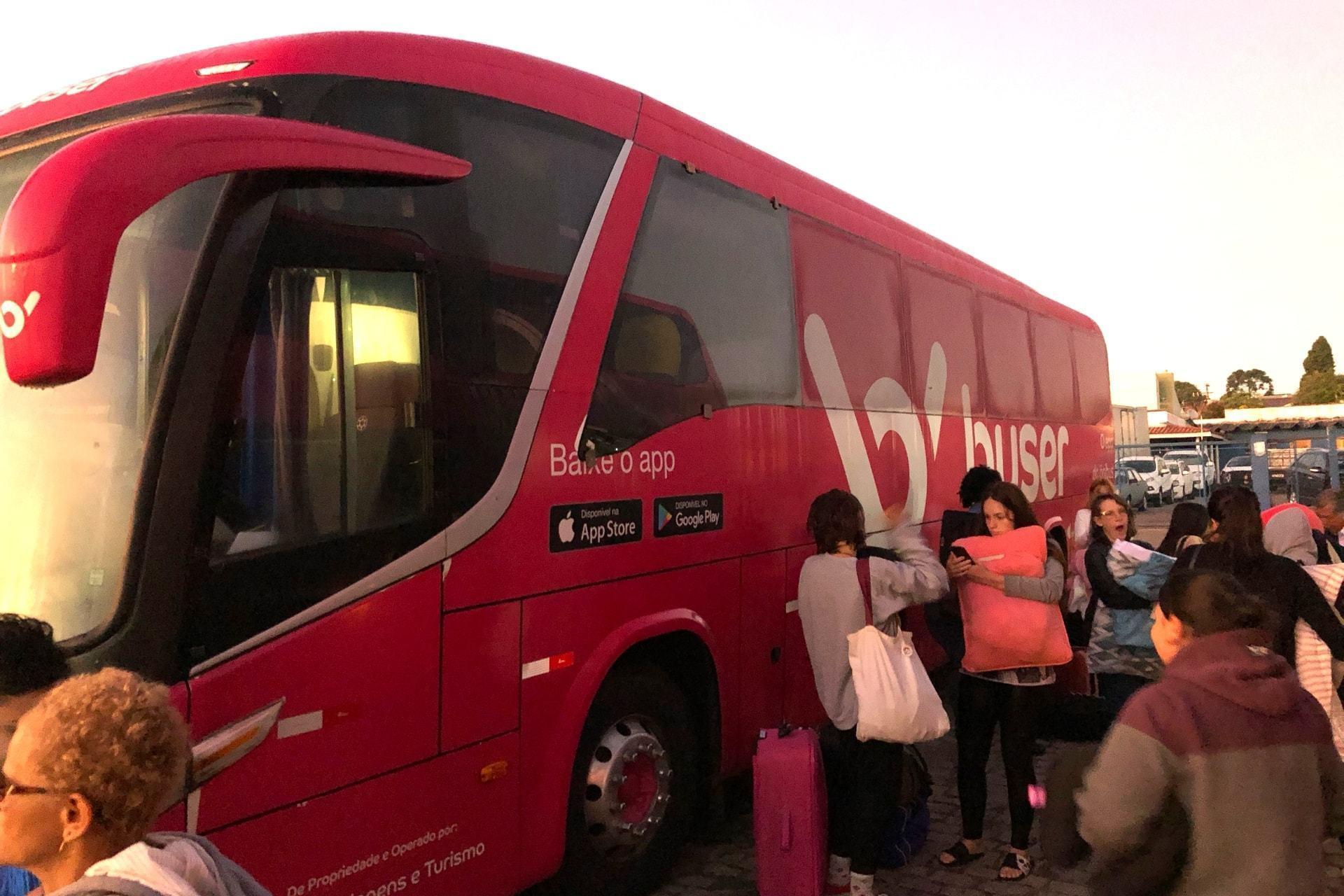 Lateral de um ônibus da Buser com alguns passageiros sonolentos ao lado.