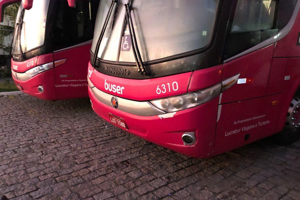 Parte frontal de dois ônibus caracterizados com a identidade visual da Buser, estacionados em um pátio.