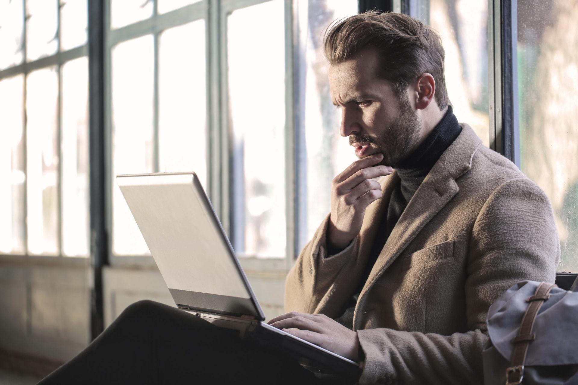 Homem branco com barba passa a mão no queixo enquanto mexe em um notebook.