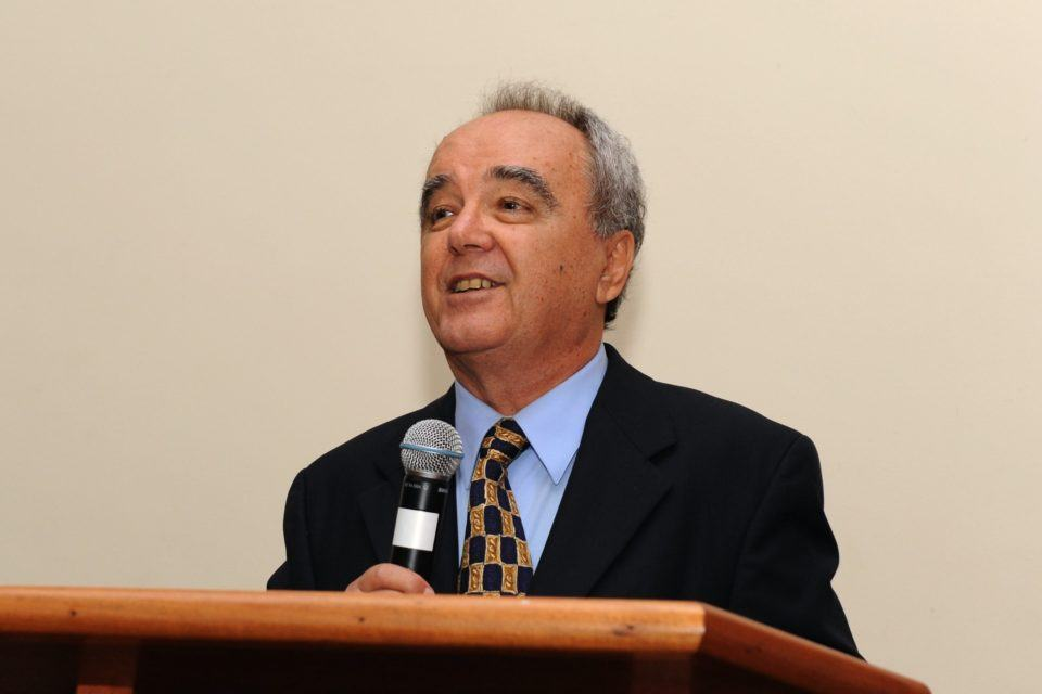 Ivan Moura Campos segurando um microfone e olhando para o lado esquerdo da imagem.