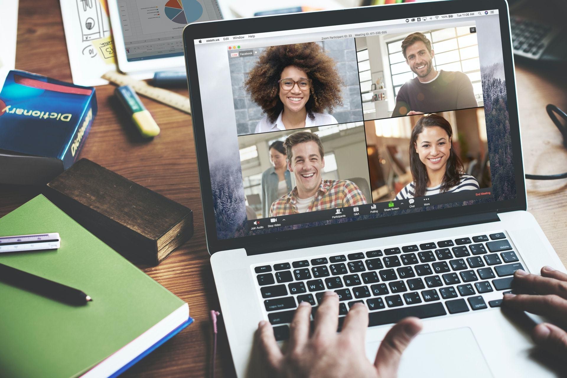 Notebook com o aplicativo da Zoom aberto com quatro pessoas participando de uma videochamada.