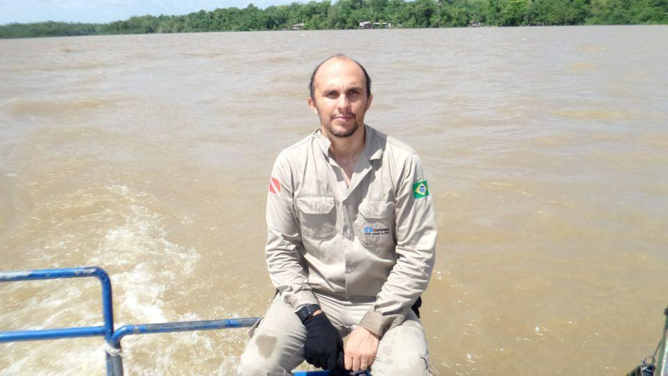 David Lopes em um barco, com um rio e o firmamento ao fundo.