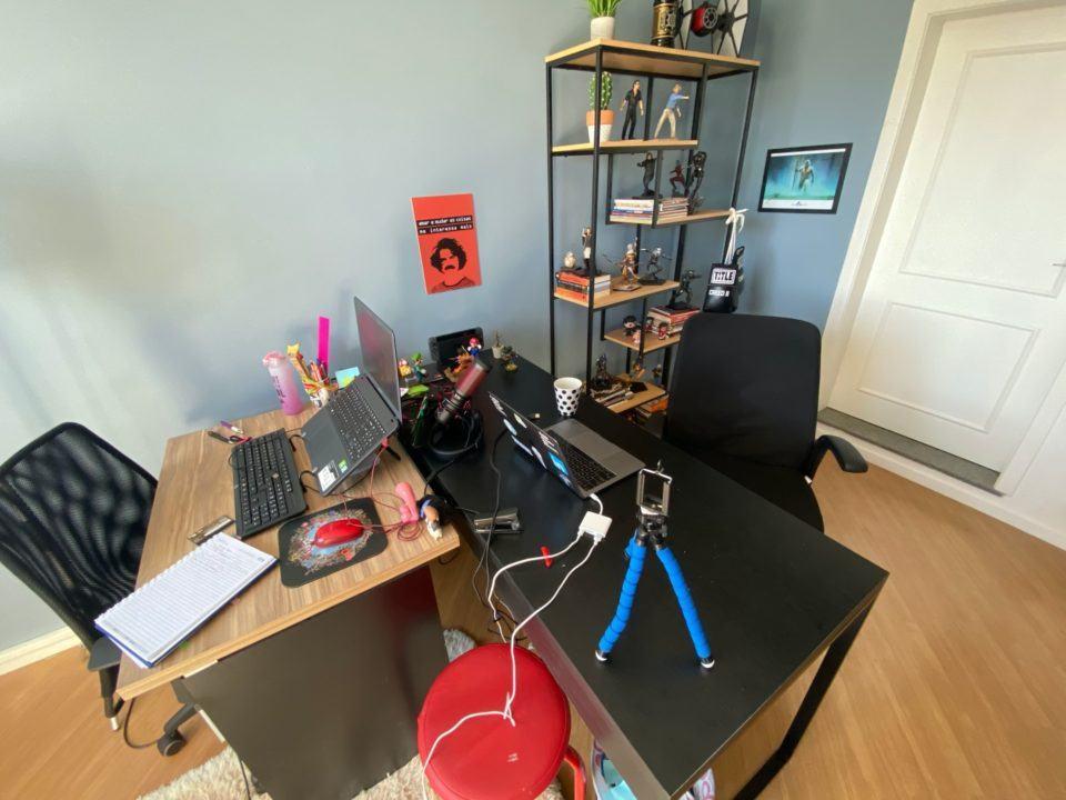 Duas mesas com notebooks e outros objetos em cima; ao fundo, uma estante com action figures; dois quadros ladeando a estante.