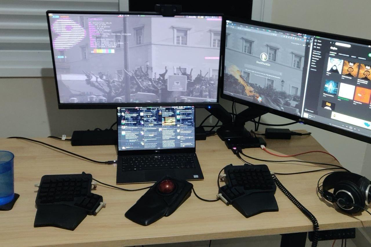 Escritório doméstico do Flávio, com notebook, dois monitores e acessórios ergonômicos sobre a mesa.
