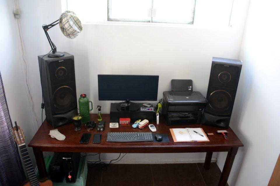 Mesa de trabalho do Rafael Goulart, com computadores, caixas de som grandes, impressora e uma janela com boa iluminação natural acima.