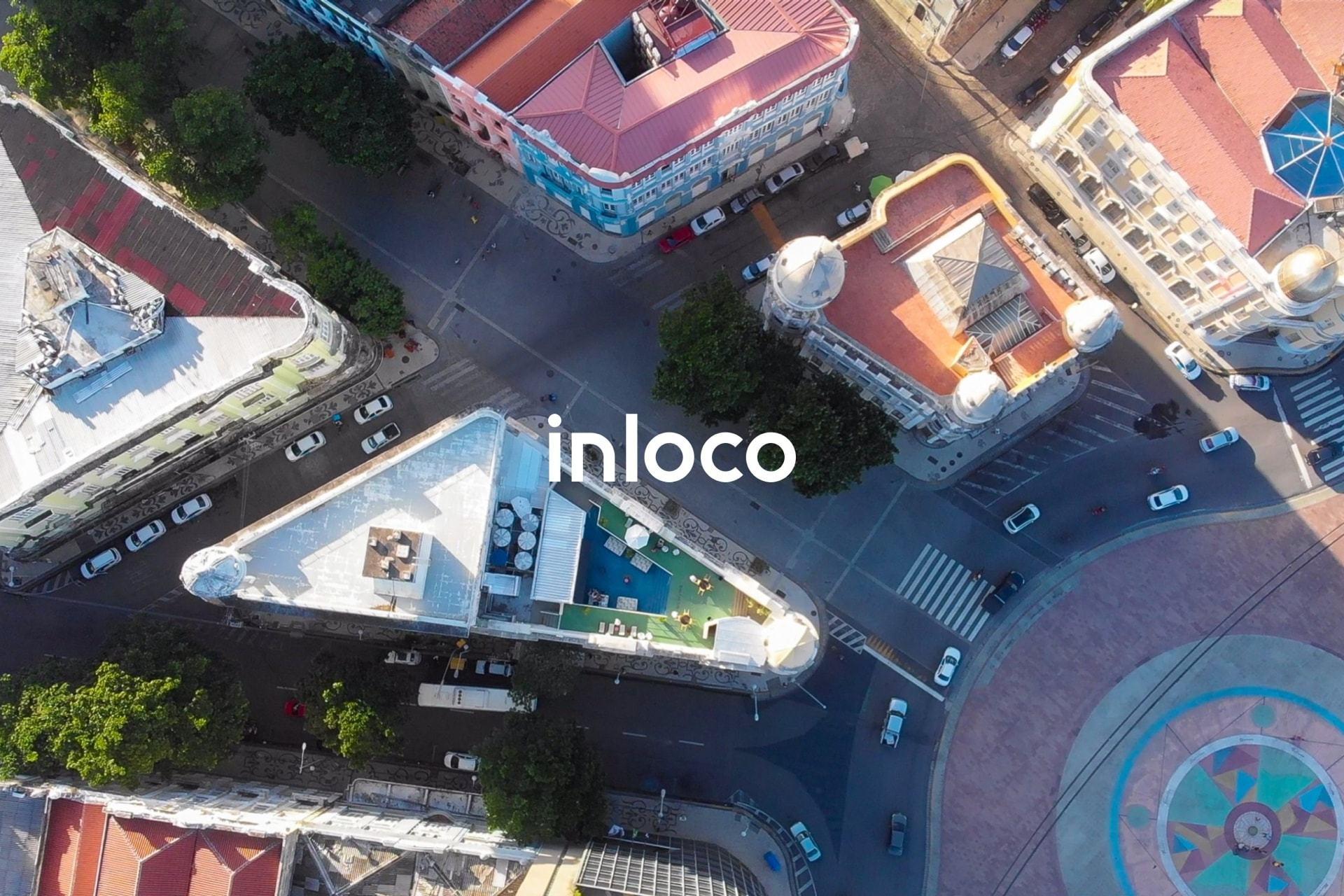 Imagem aérea de prédios e ruas com o logo da In Loco centralizado.