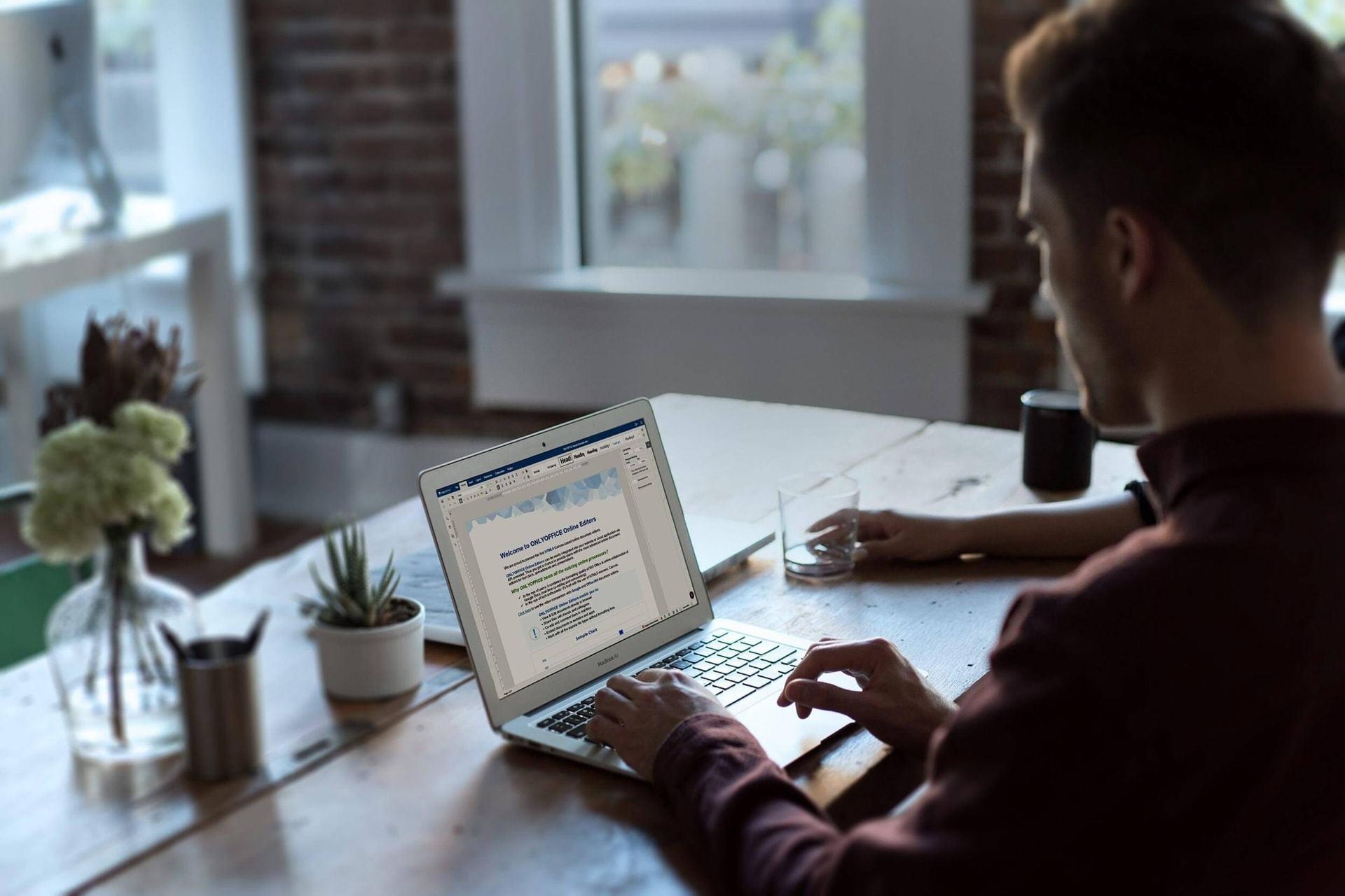 Homem de costas digitando em um notebook com um documento aberto no OnlyOffice.