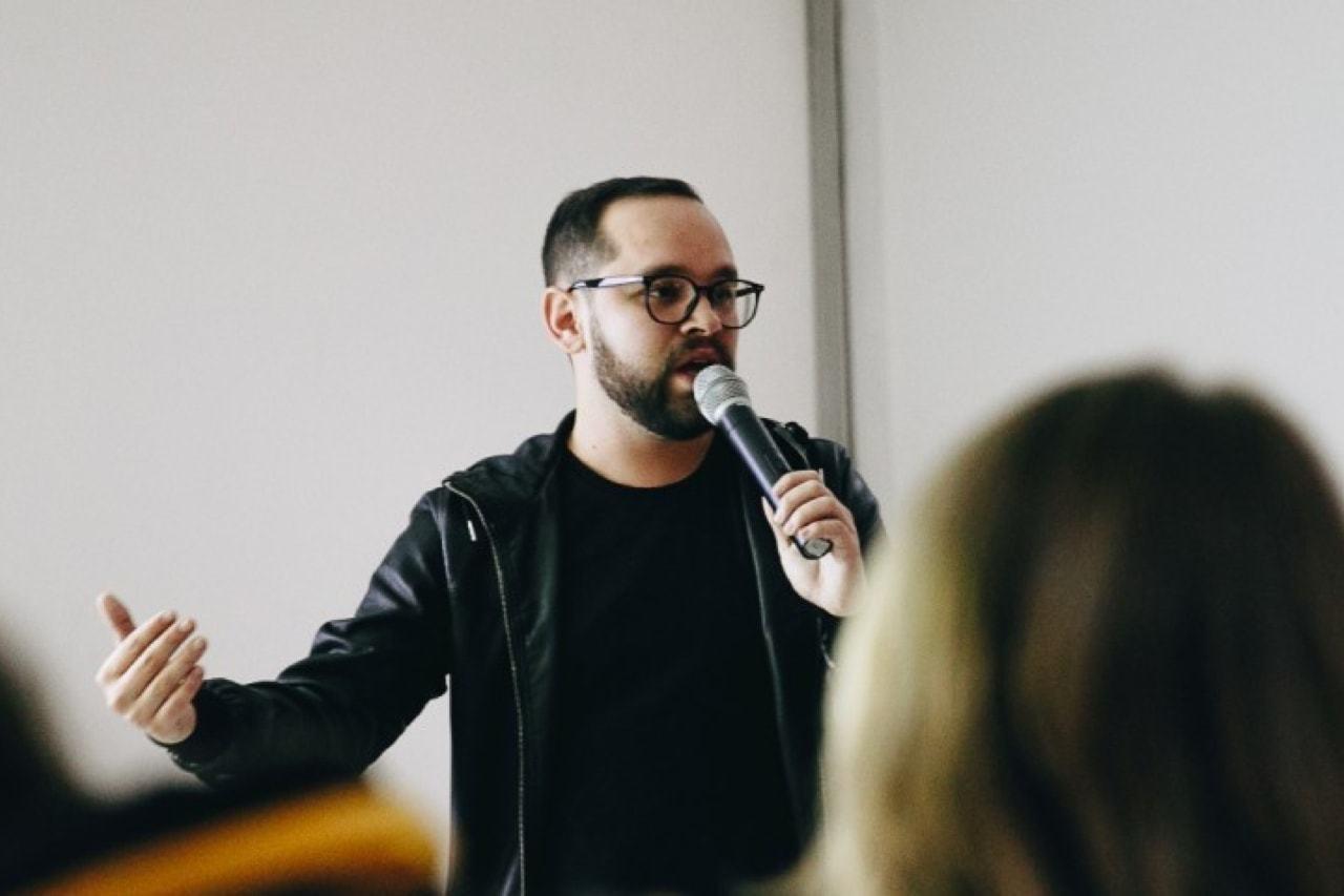 Thiago Romariz em uma apresentação segurando um microfone.