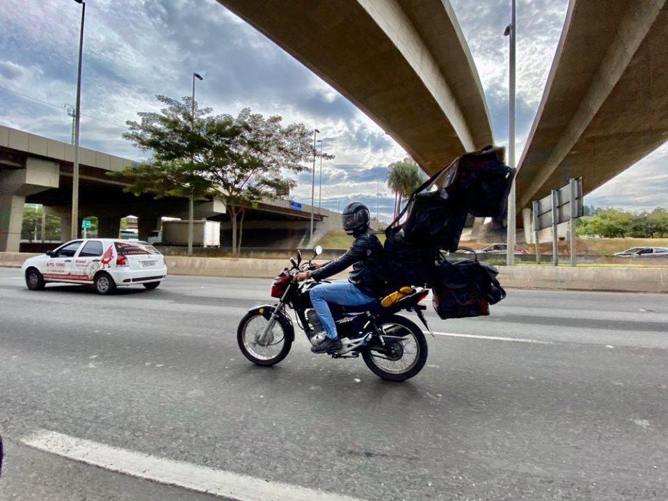 Entregador de aplicativo equilibra quatro bolsas térmicas em cima de uma moto.