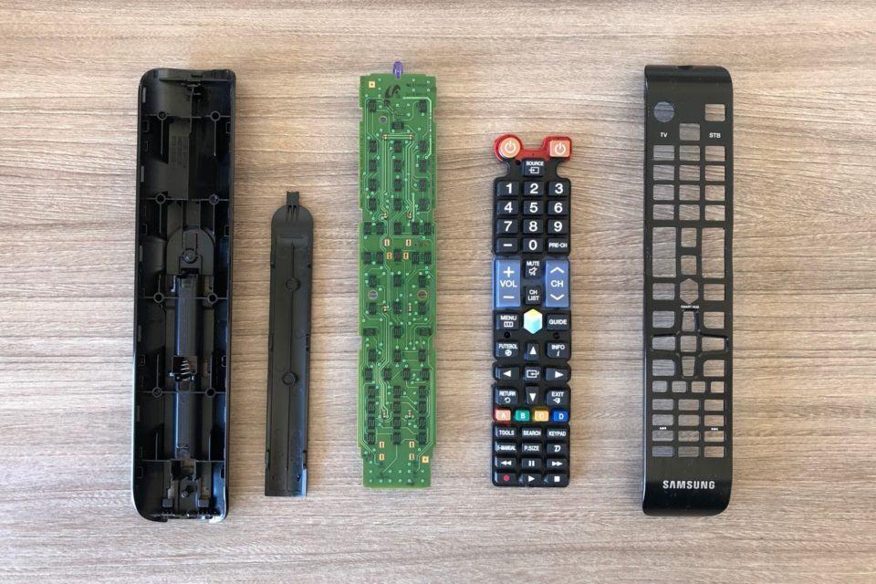 As cinco partes de um controle remoto separadas, sobre uma mesa.
