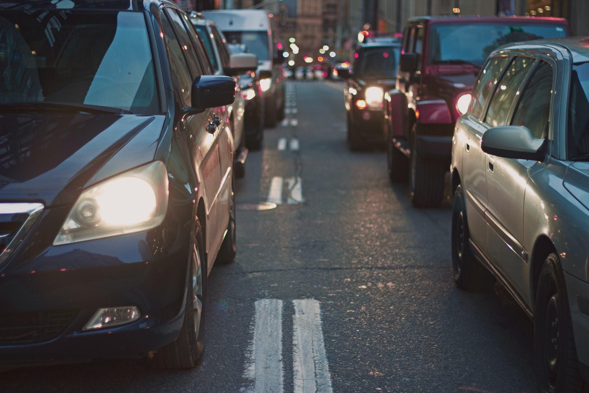 Foto frontal de duas fileiras de carros, faróis ligados, no crepúsculo.