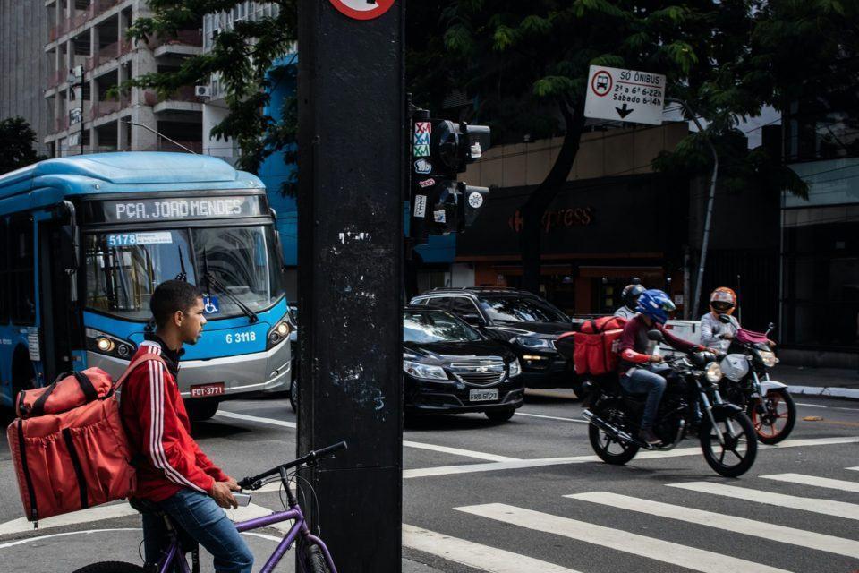 Foto de uma esquina com dois entregadores de aplicativos — um de bicicleta, outro de moto — no enquadramento.