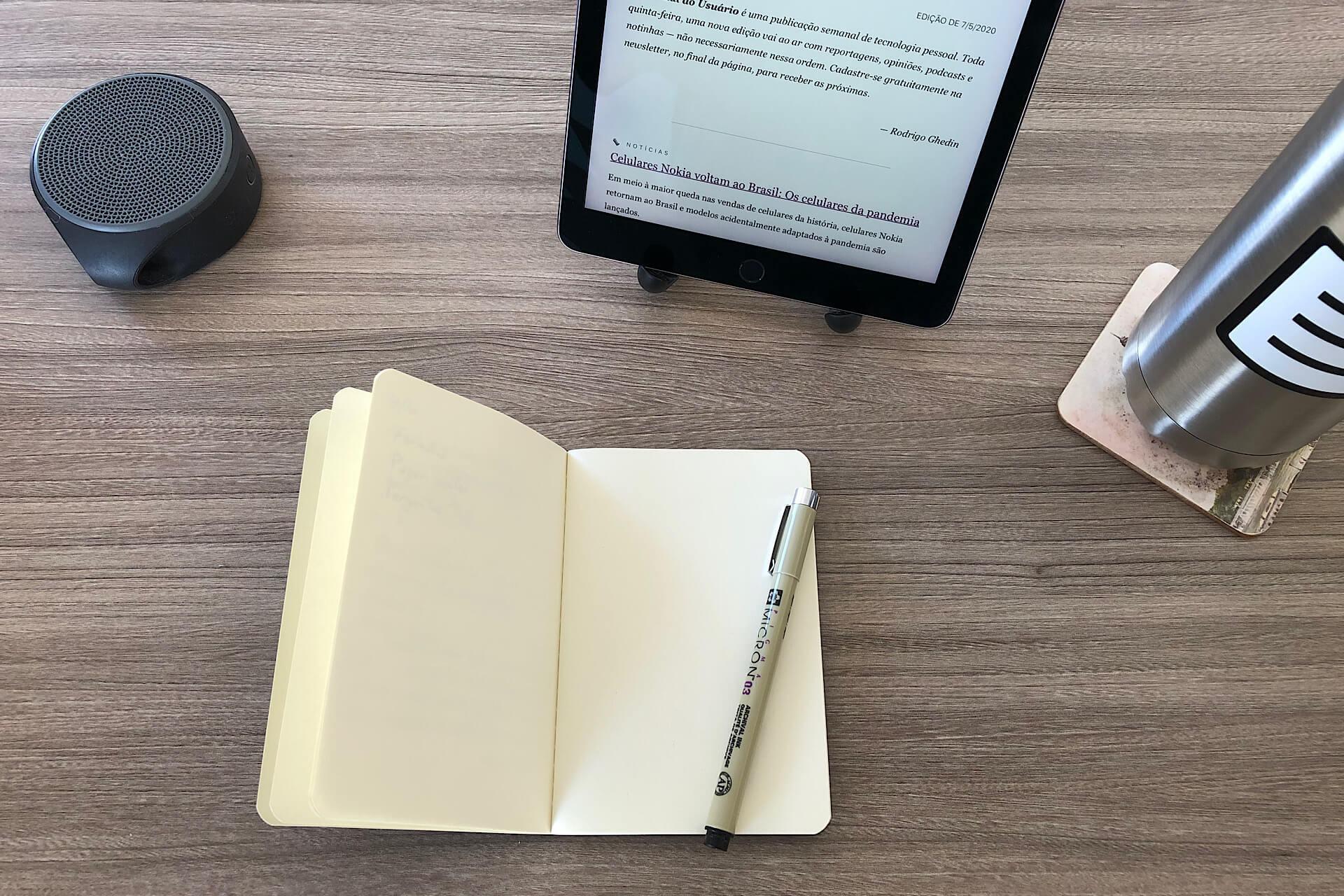 Mesa com um caderninho, caneta, tablet, caixa de som e garrafa d'água.