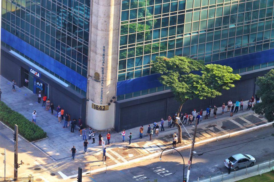 Foto aérea da fila em torno de uma agência da Caixa dobrando a esquina.
