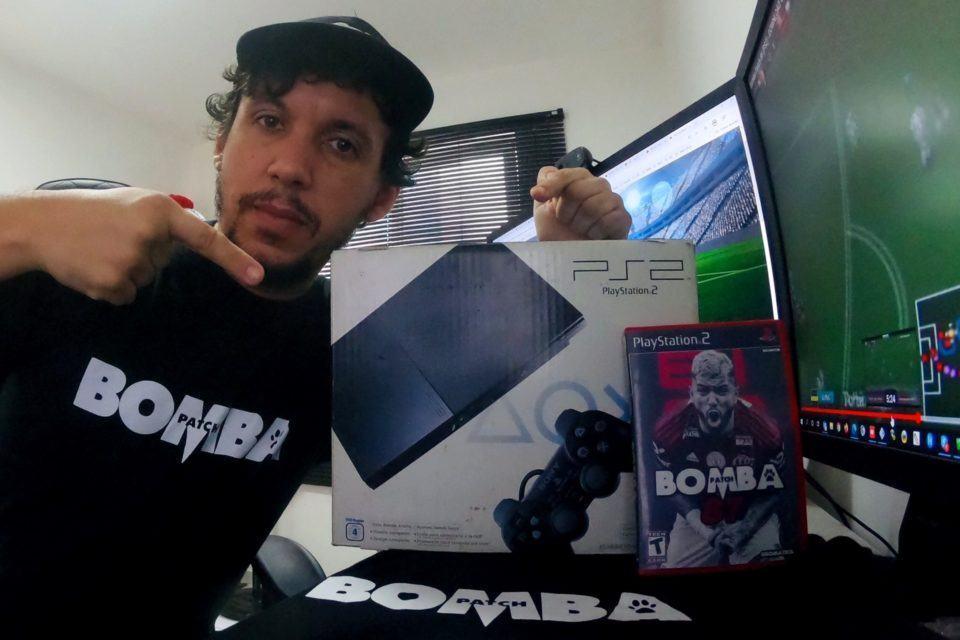 Allan Jefferson, de boné e vestindo a camisa do Bomba Patch, com um PlayStation 2, uma cópia do jogo e uma TV.