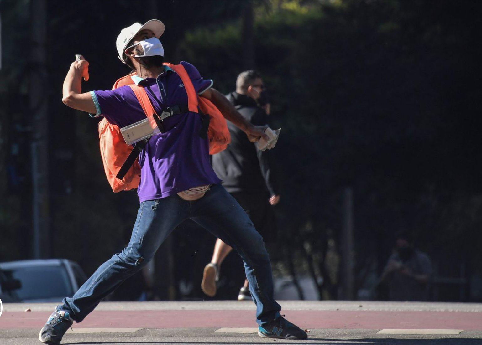 Homem pardo de máscara e com uma mochila de aplicativo de entrega arremessando uma pedra durante manifestação.